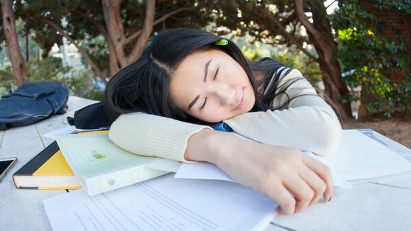 Student sleeping on a pile of books