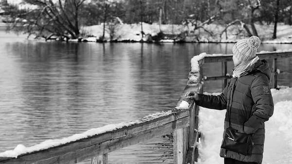 Woman standing by a lake in winter